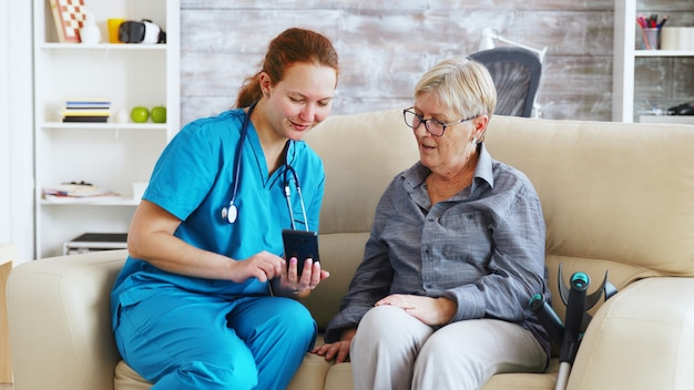 노인 여성에게 스마트폰 사용을 가르치는 소파에 앉아 있는 요양원의 여성 의사