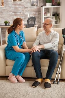 요양원의 여성 의사가 알츠하이머로 고통받는 남성과 이야기하고 있습니다.