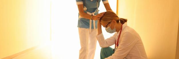 Женщина-врач в защитной медицинской маске сидит в коридоре, опустив голову, и ее поддерживает коллега. медицинская ошибка в концепции медицины