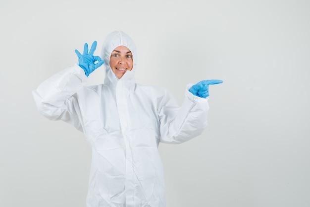 Женщина-врач в защитном костюме, перчатки, указывающие в сторону