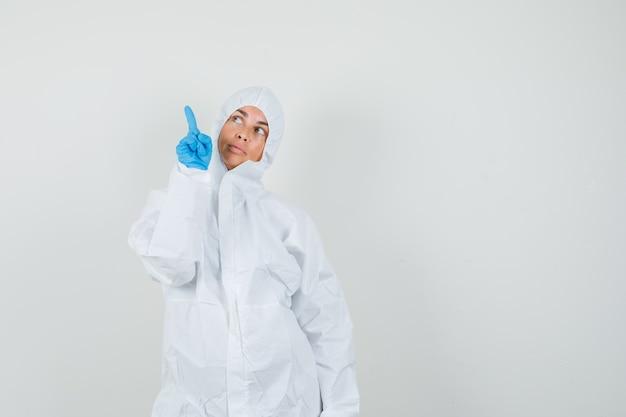 Женщина-врач в защитном костюме, перчатках вверх и с любопытством