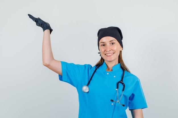 制服を着た女医、開いた手のひらを上げて喜んでいる手袋を保持