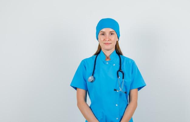 Женщина-врач в униформе улыбается и смотрит в камеру и выглядит дружелюбно