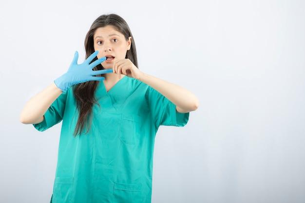 의료 장갑을 벗고 제복을 입은 여성 의사.