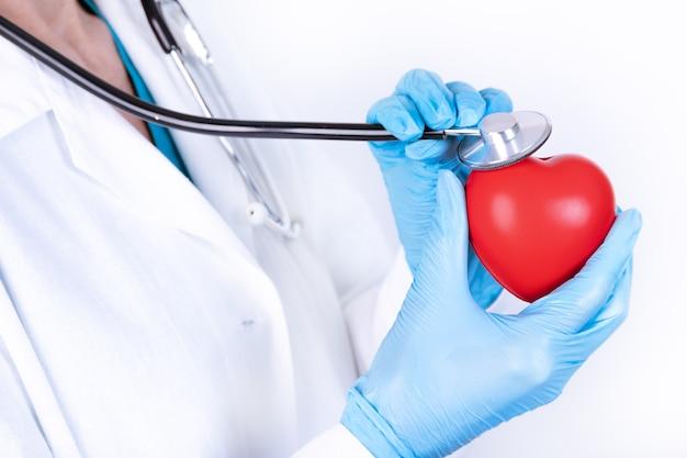 白衣と手袋をはめた女性医師が聴診器を手に持っています。