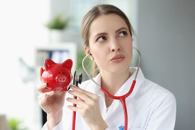흰 코트를 입은 여성 의사가 청진기를 들고 돼지 저금통에 적용합니다.