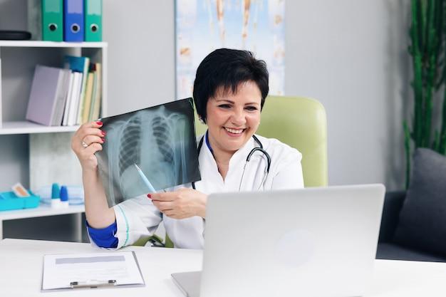 白衣を着た女性医師がノートパソコンで電話会議を行い、遠隔地の患者にビデオチャットでオンラインで相談し、ウェブカメラのコンセプトで治療を説明する