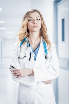 흰색 배경에 격리된 손에 청진기와 파란색 종이 홀더가 있는 흰색 외과용 코트를 입은 여성 의사
