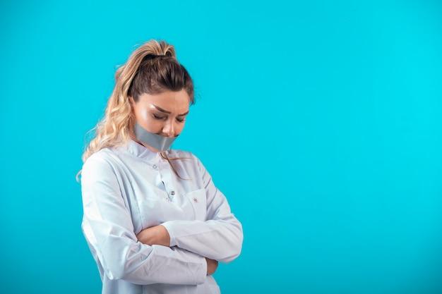 그녀의 입을 덮고 항의 흰색 제복을 입은 여성 의사.