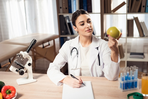 Female doctor is holding apple and writing notes