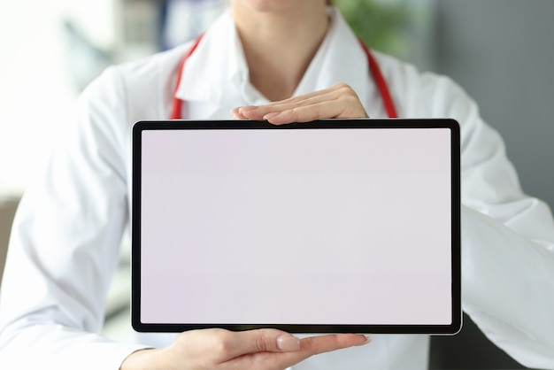 Female doctor is holding tablet with white screen