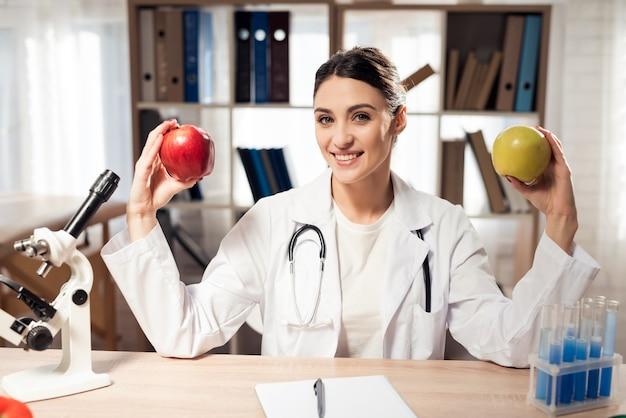 여성 의사 손에 두 개의 사과 들고있다.