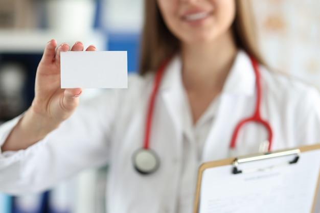女性医師は彼女の診療所の前に白い名刺を持っています
