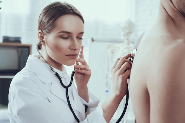Female doctor is listening to lungs with stethoscope.