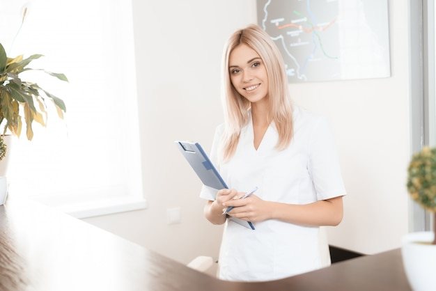 Female doctor is posing at hospital reception.