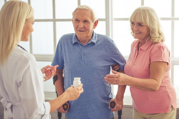 Female doctor is talking to old couple and holding a bottle