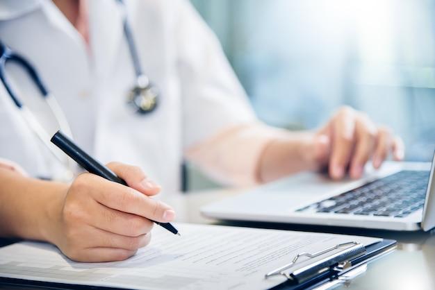 Женщина-врач использует ноутбук и пишет что-то в буфере обмена