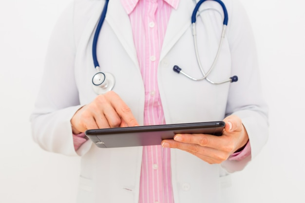Female doctor is using tablet for work. close-up.