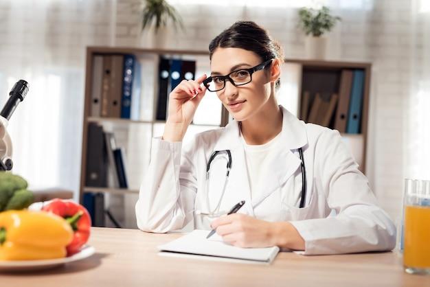 여성 의사는 노트북에 몇 가지 메모를 쓰고있다. 프리미엄 사진