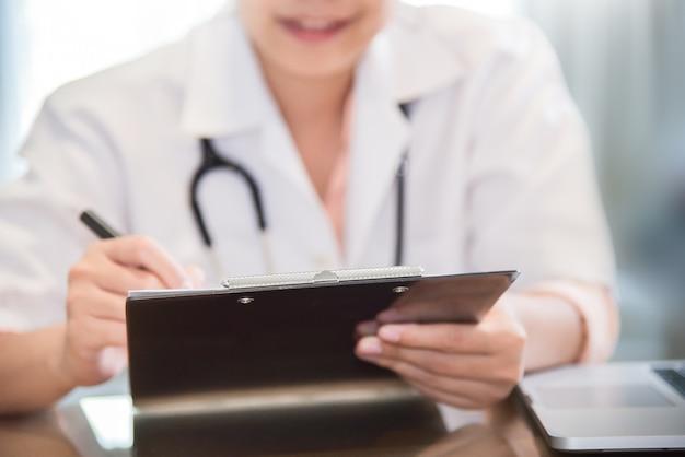 Женщина-врач пишет что-то в буфере обмена.