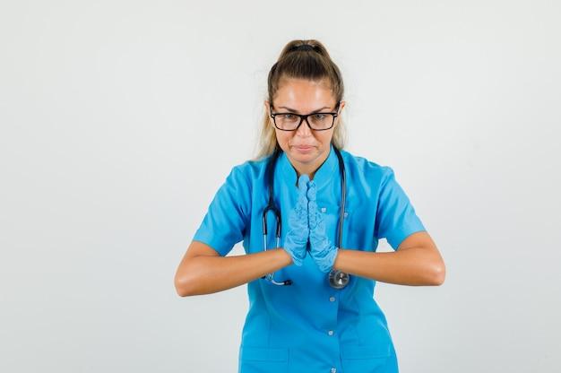파란색 유니폼에 순종을 지불하는 동안 손을 유지하는 여성 의사