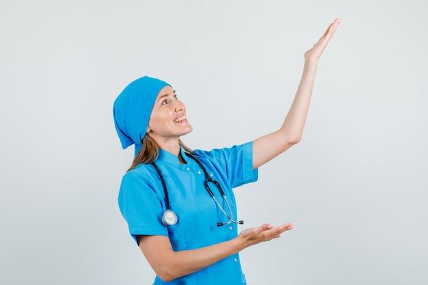 Medico femminile che tiene le palme aperte per mostrare qualcosa in uniforme e che sembra felice. vista frontale.
