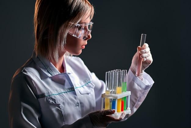 保護メガネをかけた女性の医師の検査技師は、黒で隔離された内部に多色の液体が入ったガラスの試験管が入った容器を手に持っています。