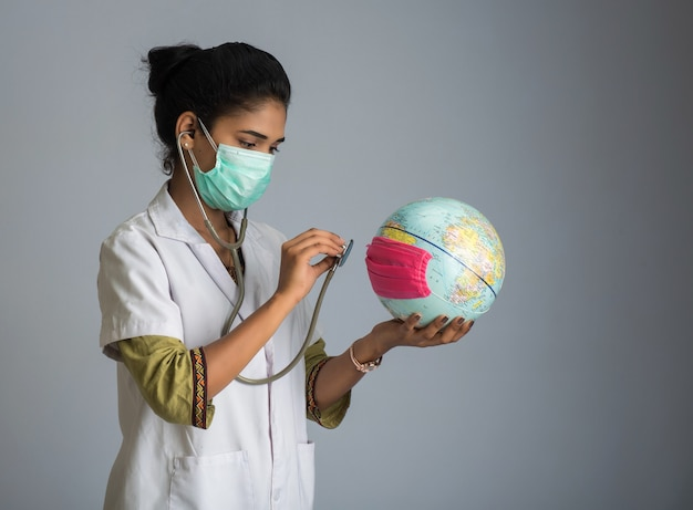 Female doctor listening to the earth globe with stethoscope