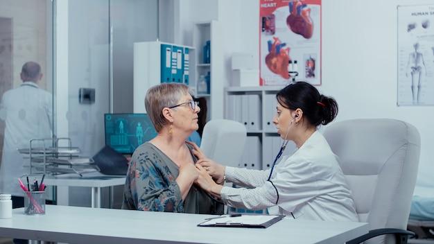 그녀의 사무실에서 노인 환자의 심장 박동을 듣고 여성 의사. 현대 병원 또는 개인 클리닉의 건강 관리, 의료 사무실 치료 약물 진단 exp에서 질병 예방 및 상담