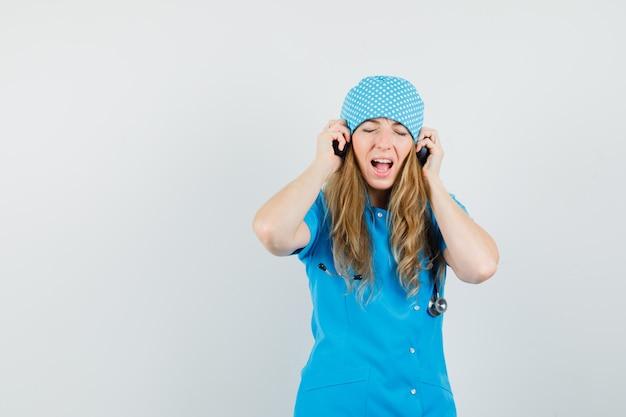 Женщина-врач слушает музыку в наушниках в синей форме и выглядит счастливой