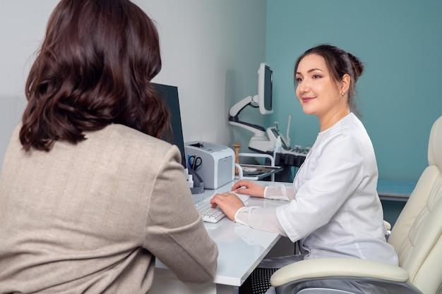 Женщина-врач выслушивает жалобы пациентки, принимая анамнез
