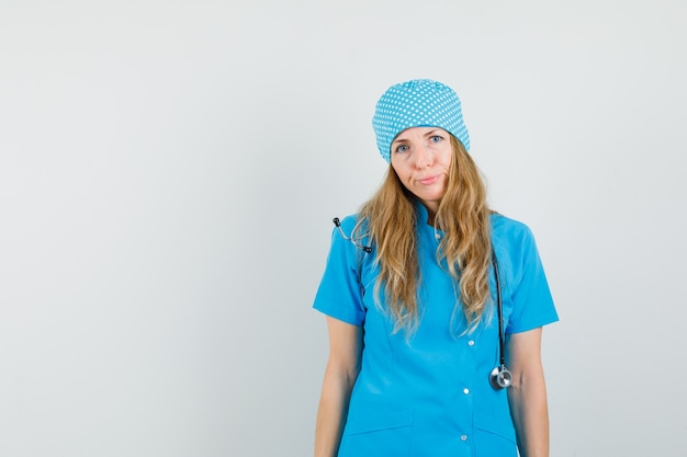 Женщина-врач смотрит в камеру в синей форме и недовольна.