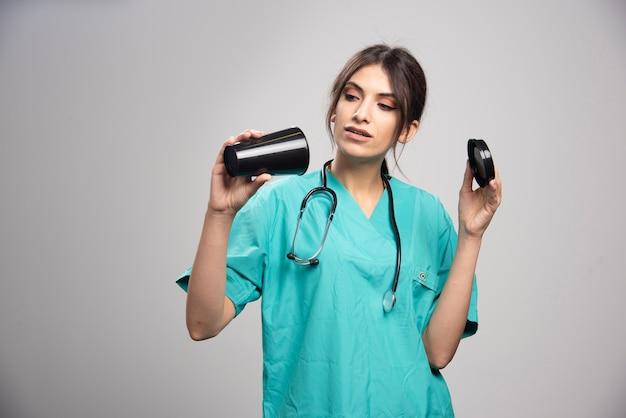 Женщина-врач смотрит на кофе на сером