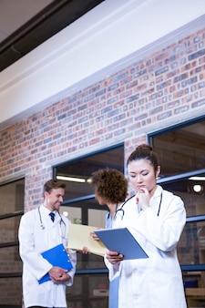 여성 의사 도서관 및 동료 뒤에 디지털 태블릿을보고 뒤에 서서 논의