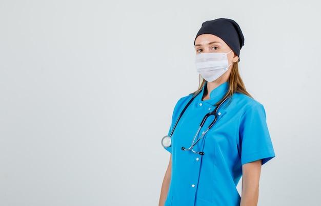 Medico donna che guarda l'obbiettivo in uniforme, maschera e guardando fiducioso. vista frontale.
