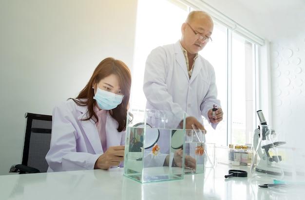 Женский доктор, глядя на аквариум и мужской доктор, держащий жидкую бутылку