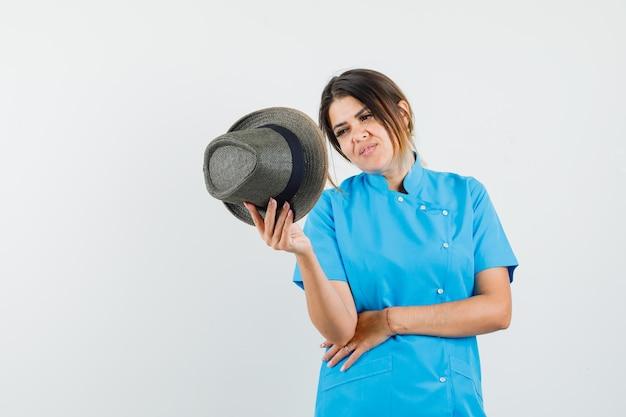 Dottoressa che guarda il cappello in uniforme blu e sembra curiosa