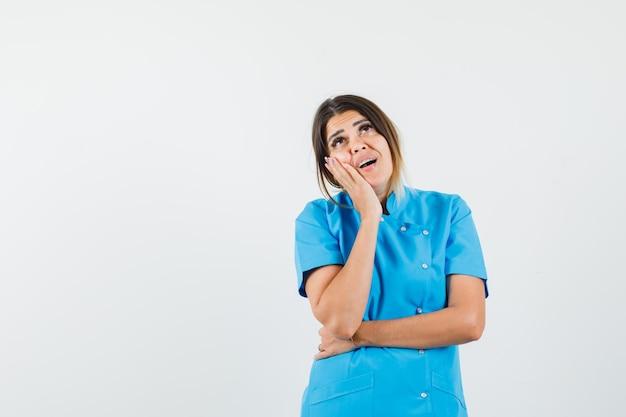 Женщина-врач смотрит вверх, прислонившись щекой к руке в синей форме и выглядит мечтательно