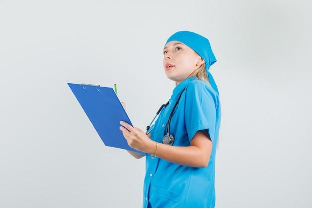 青い制服を着たクリップボードと鉛筆を持って見上げる女医師