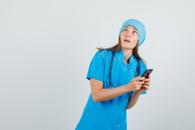 Женщина-врач смотрит вверх, держа смартфон в синей форме и смотрит сосредоточенно