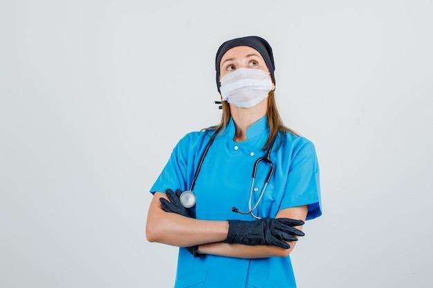 Medico femminile che osserva in su con le braccia incrociate in uniforme, maschera, guanti