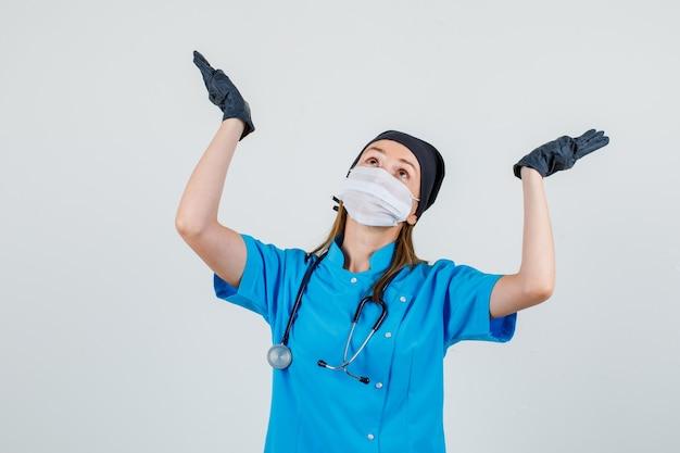 制服、手袋、マスクで上げられた手のひらで見上げ、無力に見える女性医師。正面図。