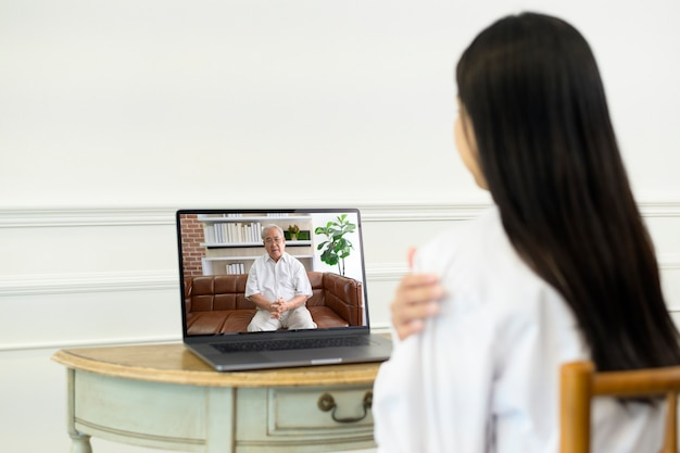 A female doctor making video call on social network with patient consulting about health problems.