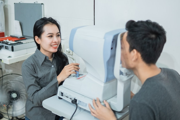 A female doctor and a male patient doing an eye check using a device at an eye clinic