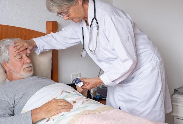 女医が自宅訪問中にベッドでひげを生やした年配の男性の血中酸素を測定する