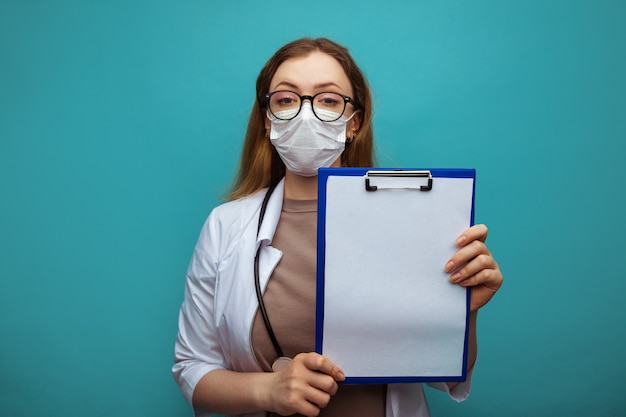 Female doctor in medical gown face mask isolated on blue