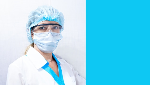 Female doctor in medical mask, hat and goggles, blue background on the right for text