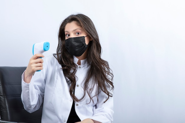 Female doctor in medical mask holding thermometer and looking at front.