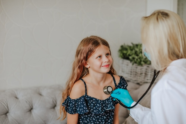 Female doctor in medical mask  seeing young patient by stethoscope.