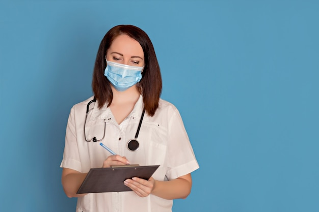Female doctor in medical mask with a stethoscope and tablet computer on blue background, copy space